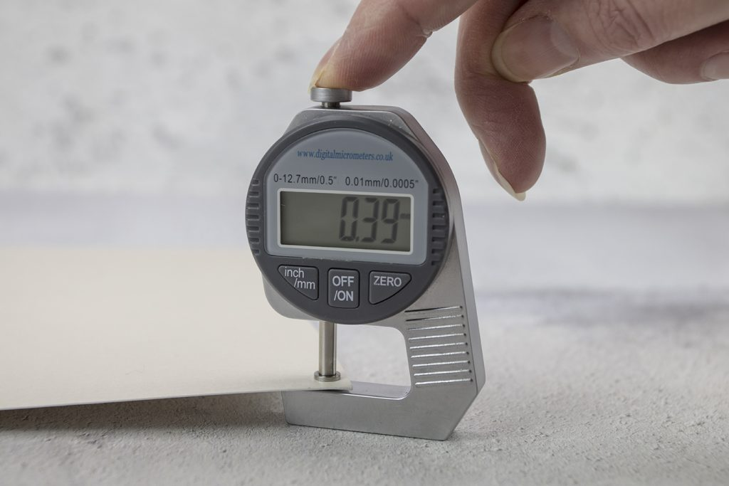 Using a digital micrometer to measure the 'mic' or thickness of the stock.