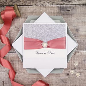 Handmade wedding invitations by Mandy Price of Elegant Creations with beautiful silver glitter and coral ribbon.