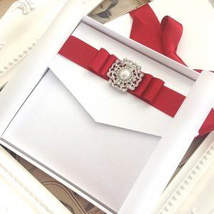 A beautifully decorated pocketfold invitation in a wedding invitation box