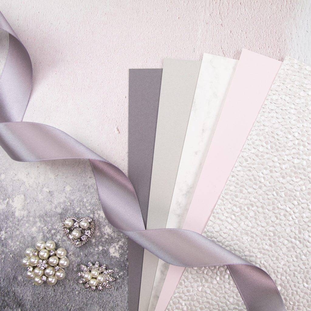 Pretty pink and grey ribbon, card and paper for wedding invitations.