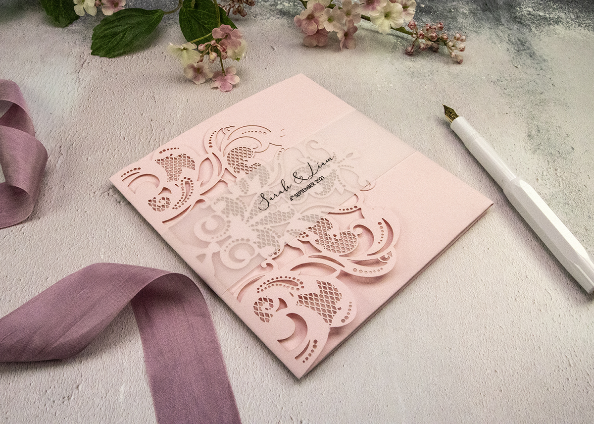 Lasercut wedding invitation with vellum belly band.