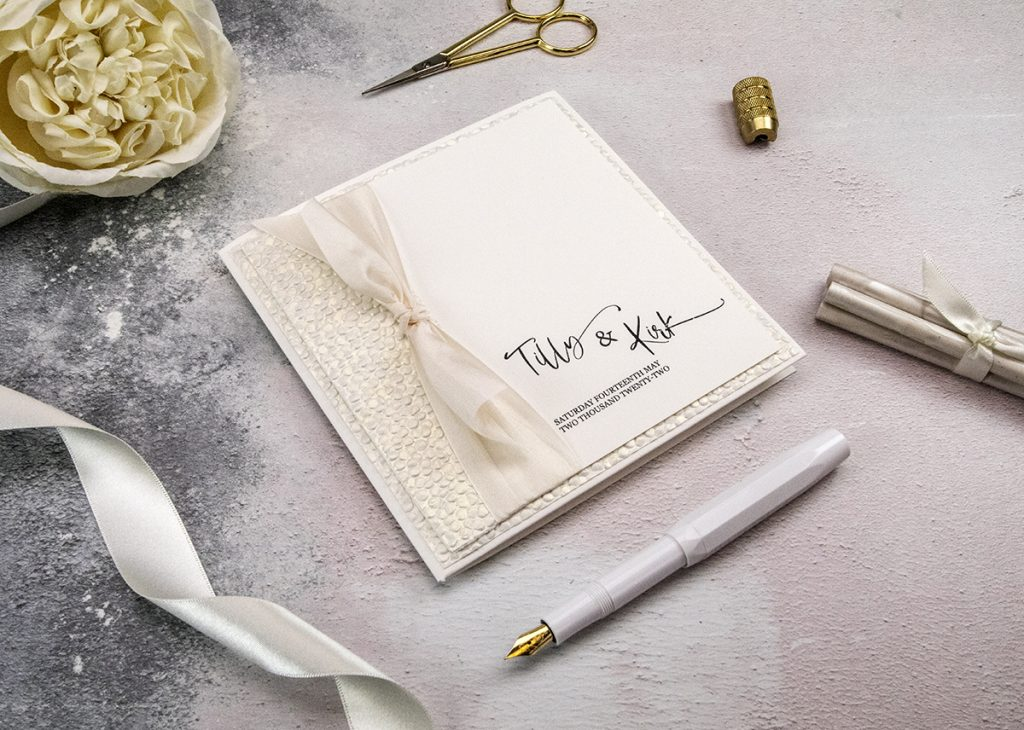 Wedding stationery with pebble paper and satin ribbon.